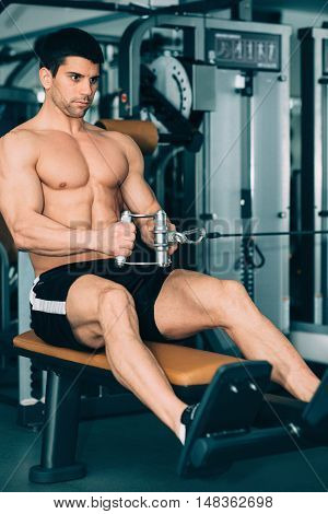 Man Exercising On Rowing Machine In Gym