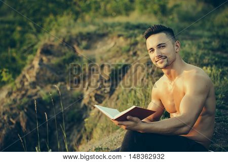 Young handsome smiling man with muscular sexy body and bare chest sitting with book outdoor sunny day