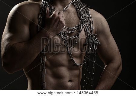 One handsome sexual strong young man with muscular body in blue jeans holding rope with hands hanging on neck and shoulders standing posing in studio on black background horizontal picture