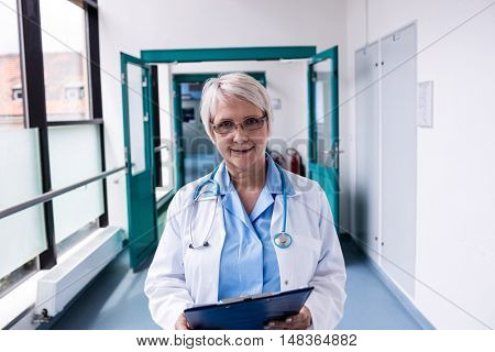 Portrait of a confident female doctor with clipboard standing in the hospital corridor
