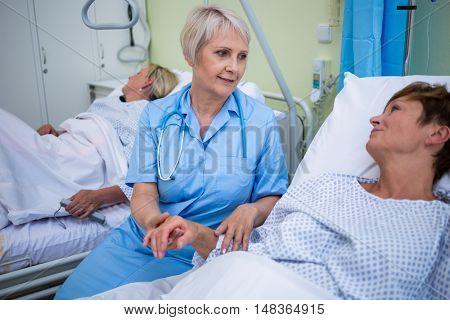 Nurse examining patients pulse in hospital room
