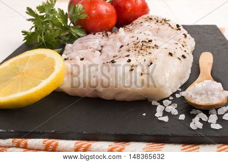 hake fillet on a slate plate with coarse sea salt a slice of lemon parsley and fresh wet tomato