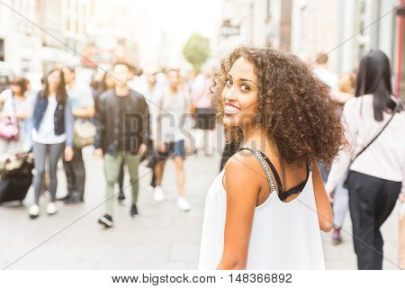 Young woman looking at camera while walking in London. Mixed race girl looking back and smiling. Blurred people on background walking on the sidewalk.