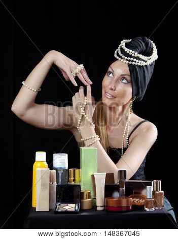 beautiful young woman in east turban with pearl beads and a lot of cosmetics on dark background