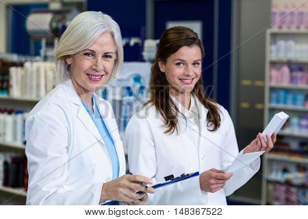 Portrait of pharmacists checking and writing prescription for medicine in pharmacy