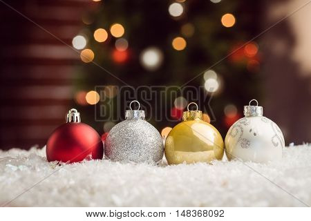 Composite image of Christmas bauble lined up against christmas tree background