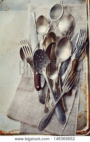 Vintage cutlery on rustic background, old kitchen tools from above, retro colors.