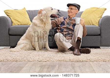 Mature man sitting on the floor and petting his dog isolated on white background
