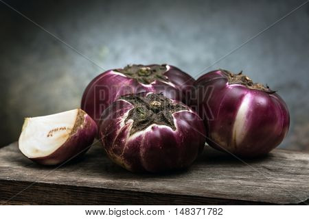 eggplant (Helios) on a wooden board. black background