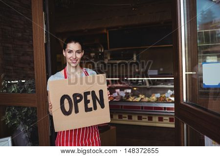 Female baker holding open signboard at the entrance of bakery shop
