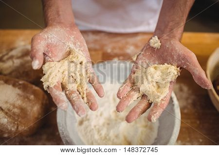 Hands of baker mixing flour by hand at bakery shop