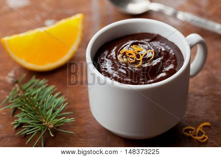 Dark chocolate mousse with orange slice decorated citrus peel and fir tree on rustic table. Delicious christmas dessert.