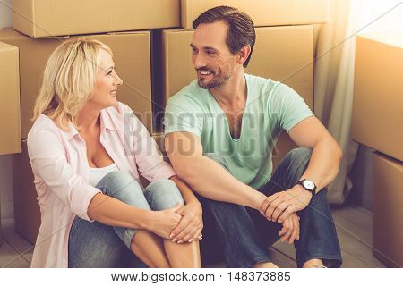 Beautiful mature couple in casual clothes is sitting on the floor among boxes talking and smiling while moving to the new apartment