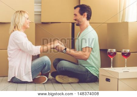 Beautiful mature couple in casual clothes is holding hands and smiling while sitting on the floor among boxes moving to the new apartment