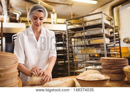 Female baker kneading a dough in bakery shop