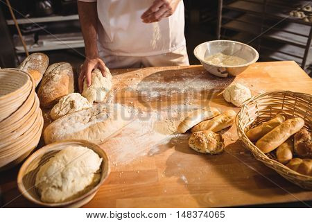 Mid-section of baker ready to knead a dough in bakery shop