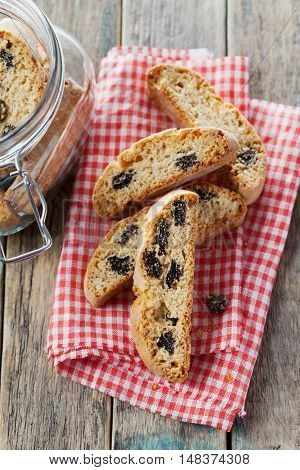 Biscotti or cantucci with raisins on wooden rustic table, traditional Italian biscuit or cookie, top view.
