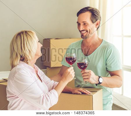 Beautiful mature couple in casual clothes is drinking wine looking at each other and smiling while standing near the boxes and celebrating moving to the new apartment