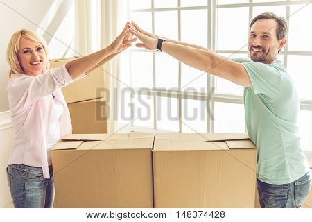 Beautiful mature couple in casual clothes is touching hands over the boxes looking at camera and smiling while moving to the new apartment
