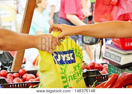 CLUJ-NAPOCA ROMANIA - SEPTEMBER 17 2016: Vendor's hands pass plastic bag to buyer at the market.