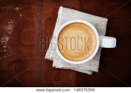 Full cup of fresh coffee on rustic wooden table, top view.