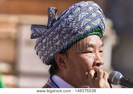 VERONA ITALY - SEPTEMBER 17 2016: Tocati International festival of street games. A musician of the Guizhou province in China plays a melody by blowing air through the mouth with a leaf