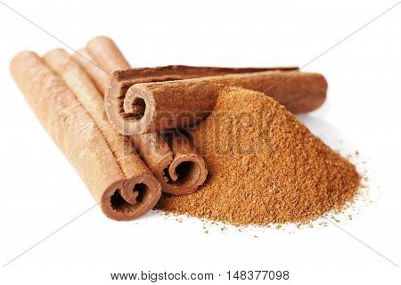 Closeup of cinnamon sticks and powder of ground cinnamon on white background.