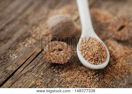 Nutmeg whole and grated on wooden background, selective focus.