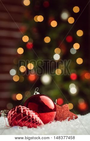 Composite image of red baubles and decorations against Christmas tree background