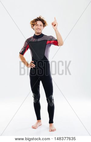 Full length portrait of a smiling happy sportsman in diving suit pointing finger up over white background