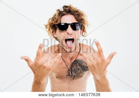 Crazy curly man in sunglasses showing tongue and rock gesture with hands isolated on the white background