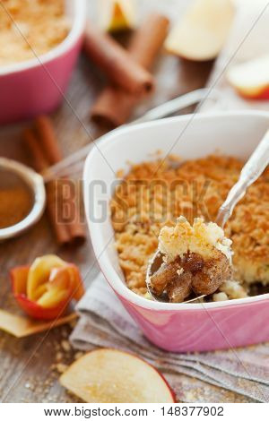 Apple crumble with cinnamon on rustic wooden table. Delicious french autumn or winter dessert for holidays.