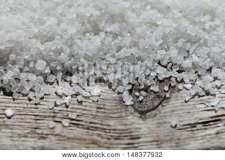 Sea salt on rustic wooden background. Macro.