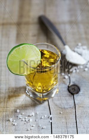 Tequila shot with lime and sea salt on rustic wooden board, selective focus.