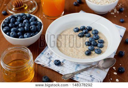 Healthy breakfast of oatmeal porridge, blueberry berries, honey and juice.