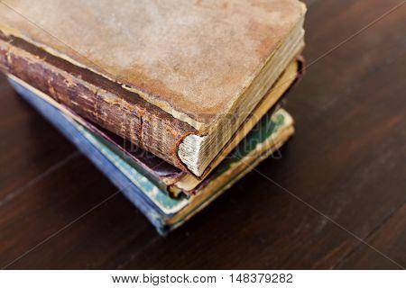 Stack of old vintage books on dark wooden background, selective focus.
