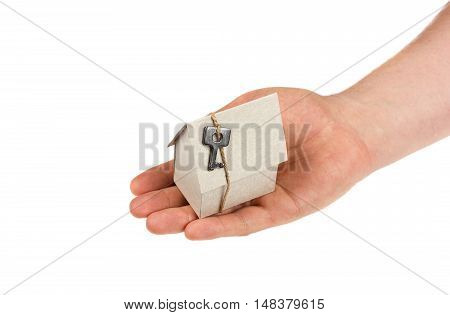 Man hand holding a model of cardboard house with key on twine isolated on white background. Building, loan, real estate or buying a new home concept.