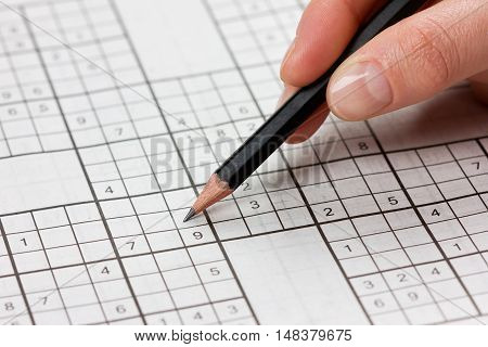 Woman hand holding a pencil and solves crossword sudoku, popular puzzle game with numbers.
