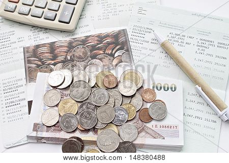 Concept of savings : Coins, money, calculator and pen on savings account passbook