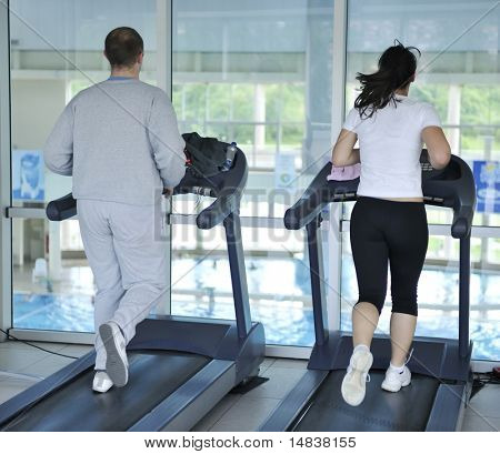 healthy people running on thread mill at sport club representing sport recreation exercise and healthy lifestyle concept
