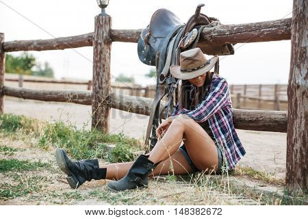 Pretty cowgirl in hat resting while leaning on the ranch fence