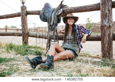 Smiling happy cowgirl in hat sitting and resting at the ranch fence