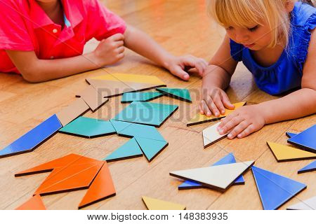 kids learning -little boy and girl playing with geometric shapes or puzzle