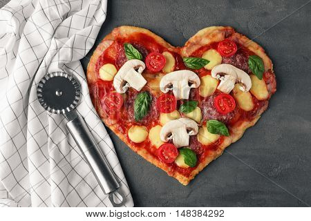 Tasty pizza in heart shape and napkin with cutter on table