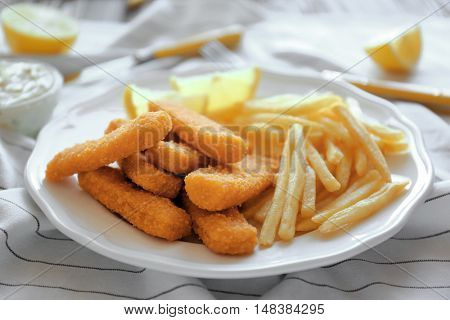 Tasty fish nuggets with lemon and fries on plate