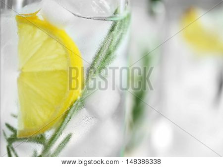Glass of cocktail with ice, lemon and rosemary closeup