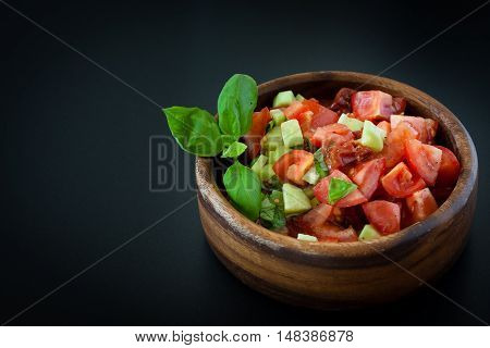 Tomato salad in a wooden bowl decorated with basil leaf