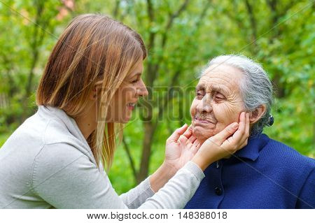Picture of proud old woman with her loving granddaughter