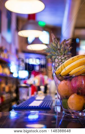 Bar At Night. Blurred Back Bar. Bowl Of Fruit On Bar Counter.