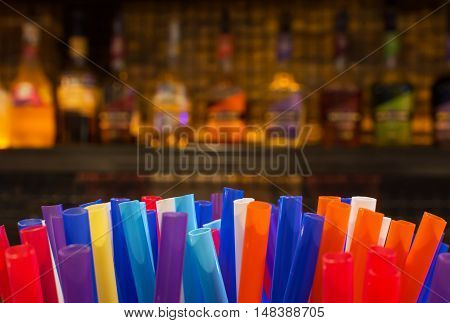 Colorful Straws And Blurred Bottles Of Spirits And Liquor In The Bar At Night